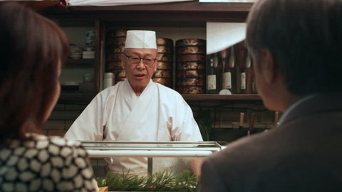 Middle aged Japanese couple using chopsticks to eat sushi while chef talks in small sushi bar with soft interior lighting. Close up shot on 4k RED camera.