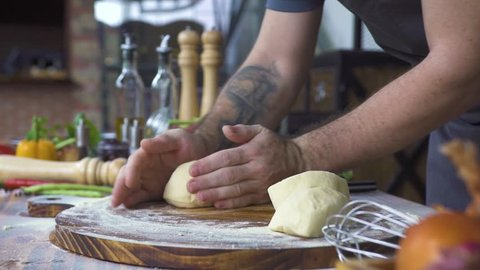 Hand of baker kneading dough for pizza preparation. Chef cook making dough for baking cake on wooden table. Process preparation homemade pastry. Cooking pasta, spaghetti, food concept