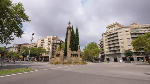 BARCELONA, SPAIN - AUGUST 12, 2018: View of Monument a Mossen Jacint Verdaguer at square, one car pass by intersection of Avinguda Diagonal and Passeig de Sant Joan. Sculpture of Catalan-language poet