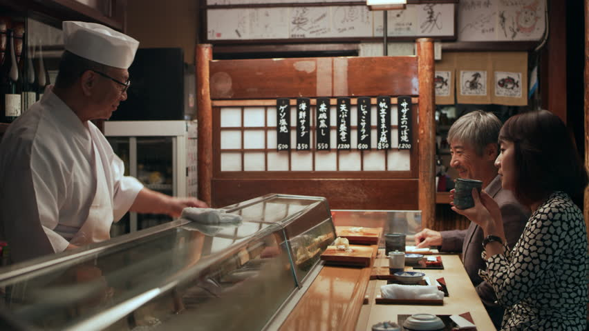 Happy Japanese couple eating sushi and watching while chef cooks in small sushi bar with soft interior lighting. Close up shot on 4k RED camera. | Shutterstock HD Video #1020021241