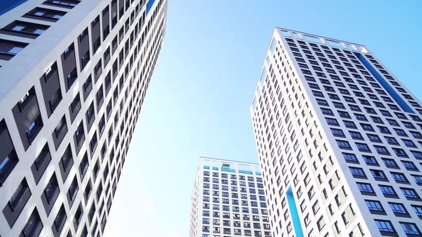 Bottom view of new residential high-rise buildings with blue sky. Urban environment. Frame. Newest residential complexes with an eco-friendly environment | Shutterstock HD Video #1020032521