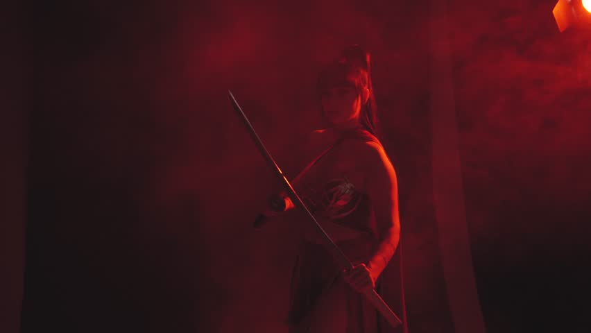 Samurai brunette girl stands alone, holds a katana weapon in hands, ready for battle, intently and attentively looks ahead through red fog, smoke, and is wearing a scarlet dress from a top and skirt | Shutterstock HD Video #1020048961