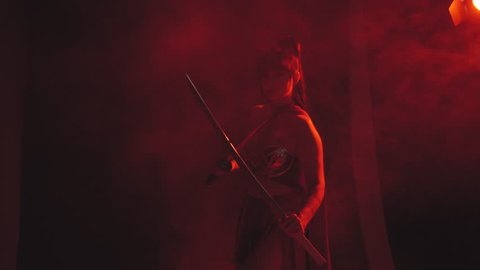 samurai brunette girl stands alone, holds a katana weapon in hands, ready for battle, intently and attentively looks ahead through red fog, smoke, and is wearing a scarlet dress from a top and skirt