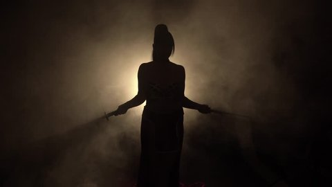 shadow of a warrior, a warrior girl with a ponytail, stands alone in a room with a dim light behind her and thick smoke, fog, crosses her swords, two katana, dressed in a red dress with gold patterns