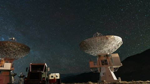 Astrophotography timelapse with pan left motion of Polaris Star over radio telescope at Owens Valley in California