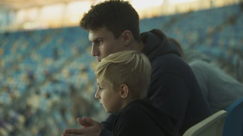 Two brothers watching football at stadium, spending time together, fellowship