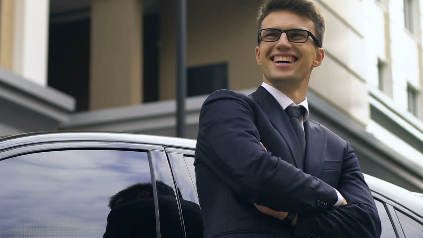 Confident businessman standing near car and happily smiling, successful deal