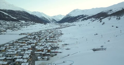 Aerial view of Italian Alps in snowy winter, mountain peaks and ski slopes covered with snow, ski resort Livigno, Lombardy, Italy from above, 4k