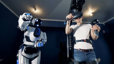 A robot copies man's movements. Robotic VR cybernetic gaming system.