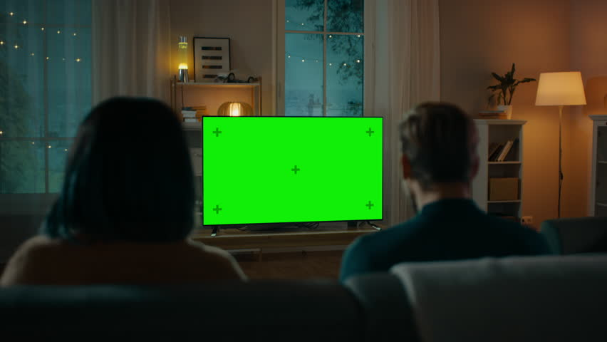 Couple Watches Green Mock-up Screen TV while Sitting on a Couch in the Living Room. Romantic Evening for Boyfriend and Girlfriend. | Shutterstock HD Video #1020143911