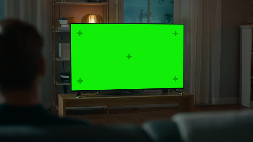 Man Watches Green Mock-up Screen TV while Sitting on a Couch at Home in the Evening. Cozy Living Room with Warm Lights. Over the Shoulder Shot.