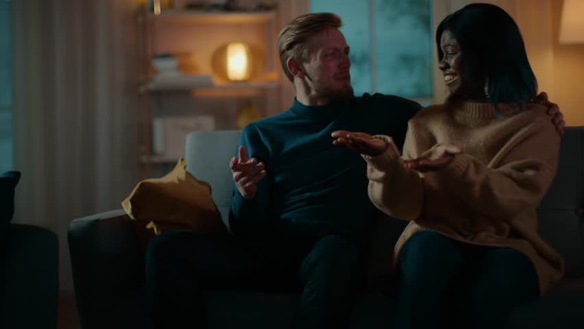Happy Diverse Young Couple Watching Comedy on TV while Sitting on a Couch, they Laugh and Enjoy Show. Handsome Caucasian Boy and Black Girl in Love Spending Time Together. Moving Camera Shot. | Shutterstock HD Video #1020145081