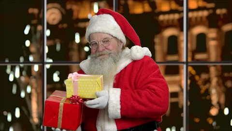 a0ac9444bca25 Santa Claus with gifts showing thumb up. Old authentic Santa Claus on  evening city background