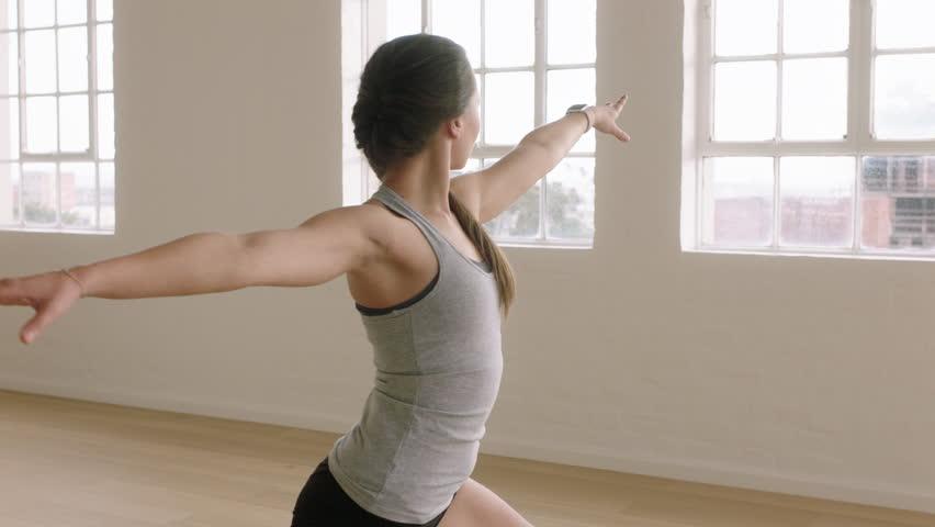healthy yoga woman practicing warrior pose enjoying fitness lifestyle exercising in workout studio stretching training on exercise mat at sunrise #1020189571