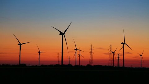High speed footage of wind turbines rotating in the wind at sunset in a field.