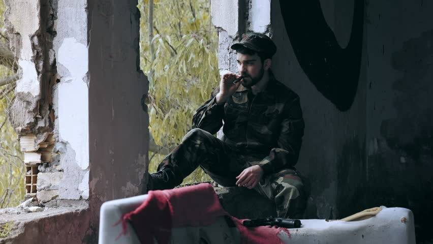 young man with soldier dresses sitting alone and smokes a cigar #10202021
