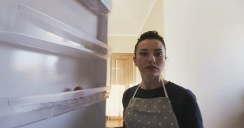 Attractive Woman opens door of an empty refrigerator surprised POV view from inside the fridge and gets disappointed without food in the Kitchen shot on RED camera