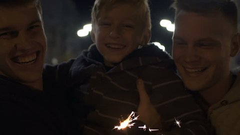 Cheerful gay family with adopted son celebrate guy Fawkes night, happy together
