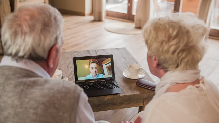 Boy waving over video call with grandparents HD. Over shoulder view of elderly couple calling grandson with video call on laptop computer. Laptop on wooden desk. Two person sit on sofa.   Shutterstock HD Video #1020255901