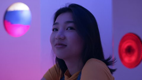Cool Japanese woman sitting at a bar looking at the camera in a fun bar with soft interior lighting. Medium shot on 4k RED camera on a gimbal.