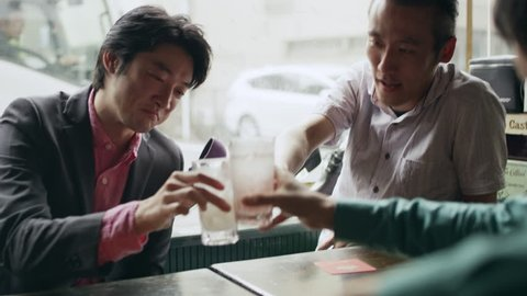 Japanese friends sitting at a table with their drinks talking happily and having fun in a cool bar with soft natural lighting. Medium shot on 4k RED camera.