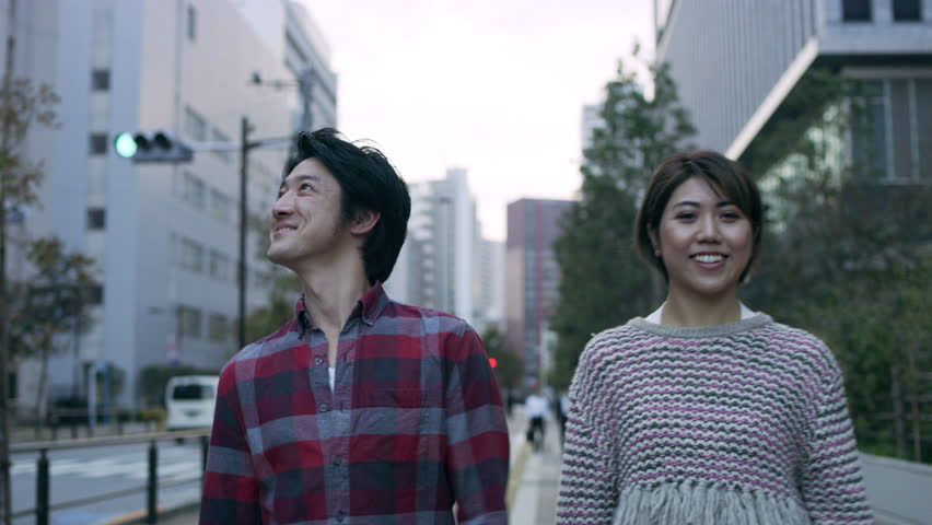 Smiling Japanese couple walking down a quiet metropolitan street with soft natural lighting. Medium shot on 4k RED camera. | Shutterstock HD Video #1020280981