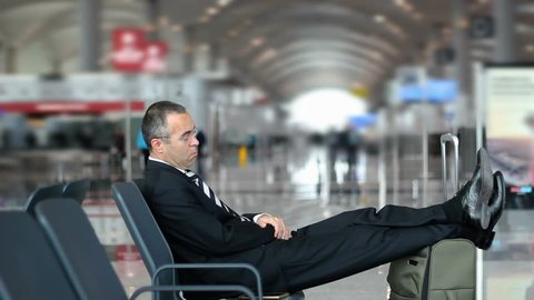 Passenger business man sleeping in the airport, waiting for flight