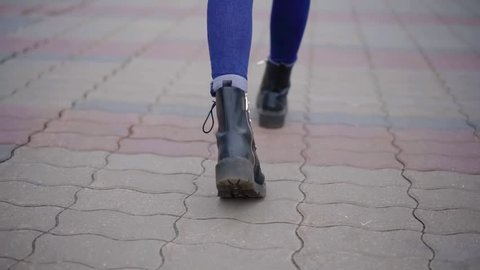 woman is walking in city in daytime in autumn, close-up view of her shoes from back, strolling