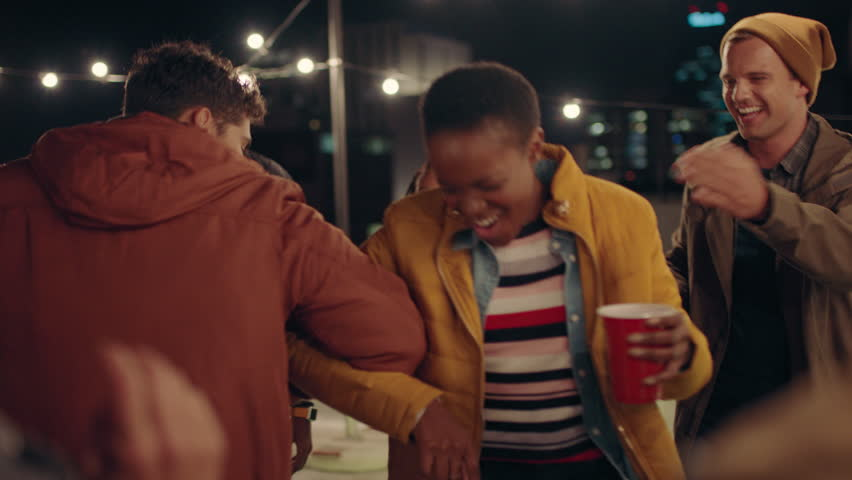 Young group of multiracial friends having fun dancing playfully together enjoying rooftop party at night laughing celebrating friendship | Shutterstock HD Video #1020300991