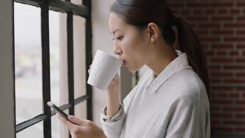 beautiful asian business woman drinking coffee at home using smartphone enjoying relaxed morning browsing messages looking out window planning ahead texting on mobile phone networking