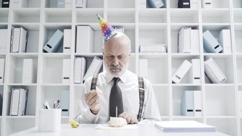 Sad businessman celebrating a lonely birthday in the office, he is blowing a candle on a small cake
