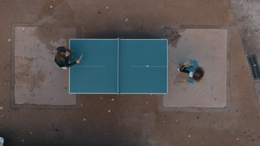 Clean and minimal top drone footage of two best friends or student young girls have fun outdoors. Play ping pong or table tennis in park playground. Laugh and smile in friendly competition game #1020360211