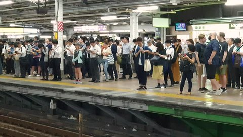 Tokyo, Japan - August 2018: Train arriving at a subway station platform while commuters wait in line