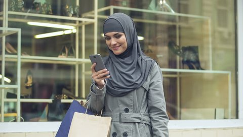 Happy Arabic lady using online shopping app for searching discounts, fashion
