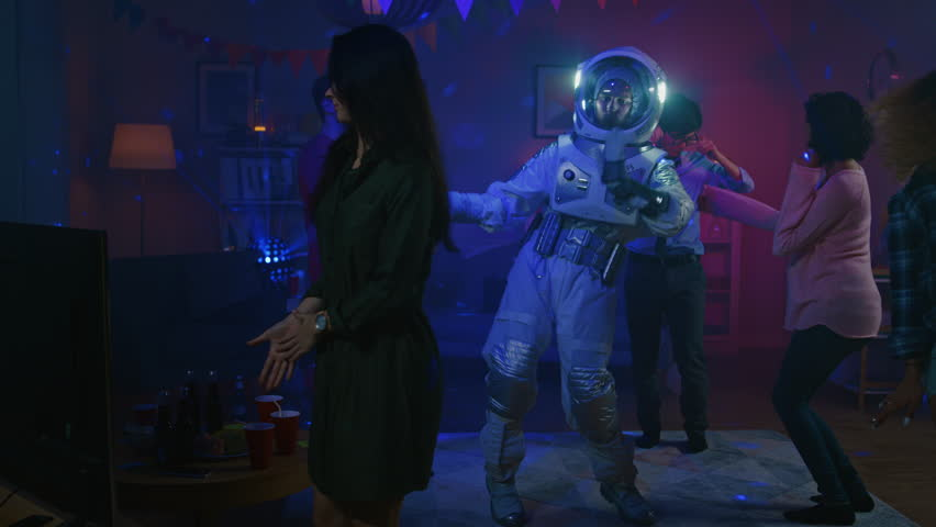 At the College House Costume Party: Fun Guy Wearing Space Suit Dances Off, Doing Groovy Funky Robot Dance Modern Moves. With Him Beautiful Girls and Boys Dancing in Neon Lights. | Shutterstock HD Video #1020544111