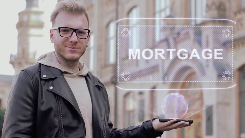 Smart young man with glasses shows a conceptual hologram Mortgage. Student in casual clothes with future technology mobile screen on university background