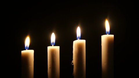 Footage of white candles flicker in the darkness. Christmas