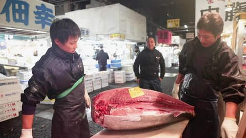 tokyo, Japan - 01 10 2018: A man sliceing a big tuna fish in the Tsukiji fish market in Tokyuo, Japan.