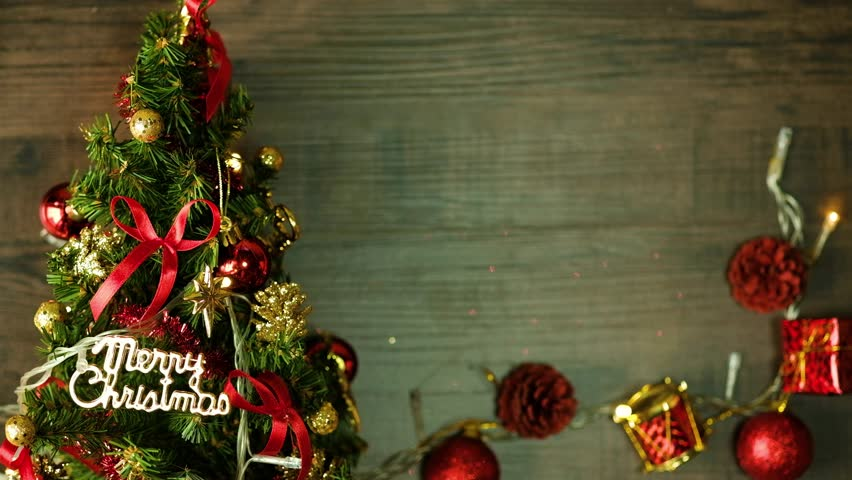 Wooden table decorated with Christmas stuff and Christmas tree. Christmas lights. | Shutterstock HD Video #1020702181