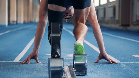 A runner with prosthetic leg training, back view.