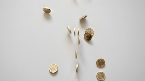 Many British currency 1 pound coins rolling across the white background frame, some of them falling. Race, competition concept