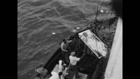 1940s: Clouds hang over the ocean. Ropes lower man on gurney to lifeboat. Men on lifeboat help injured man on gurney onto lifeboat.