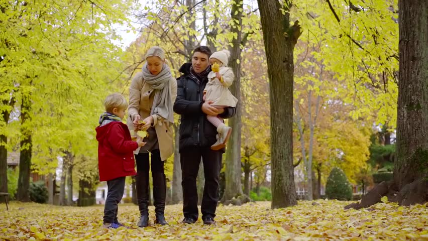 Father mother and two children enjoying lovely family walk in autumn park. | Shutterstock HD Video #1020728131