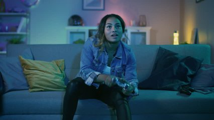Beautiful Excited Young Black Gamer Girl Sitting on a Couch, Playing and Winning in Video Games on a Console. She Plays with a Wireless Controller. Cozy Room is Lit with Warm and Neon Light.