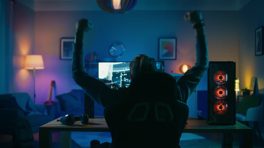 Back Shot of a Gamer Playing and Winning in First-Person Shooter Online Video Game on His Powerful Personal Computer. Room and PC have Colorful Neon Led Lights. Cozy Evening at Home. | Shutterstock HD Video #1020758401