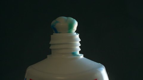 Squeezing toothpaste from tube slow motion closeup