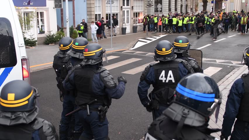 STRASBOURG, FRANCE - DEC 8, 2018: Police officers securing the zone in front of the Yellow vests movement protesters on Quai des Bateliers street - overhead view