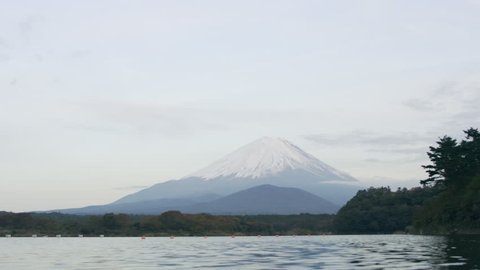 View of Mount Fuji in the distance over the water with soft natural lighting. Wide shot on 4k RED camera.