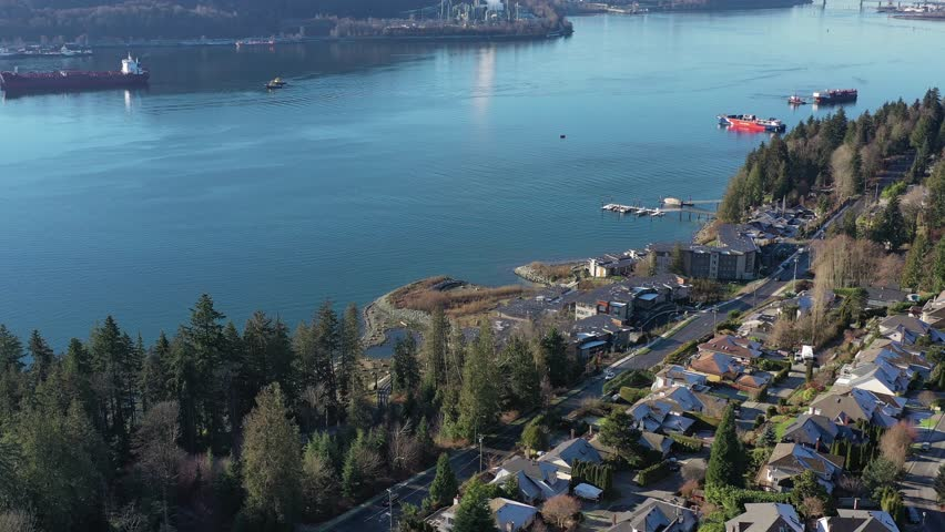 Aerial view over Burrard Inlet, ocean and island with boat and mountains in beautiful British Columbia. Canada. | Shutterstock HD Video #1020790441