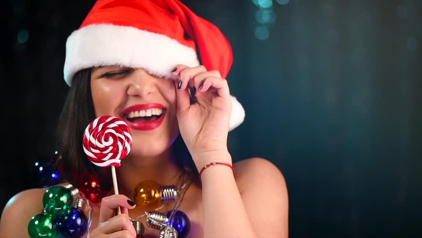 Christmas Woman in Santa hat laughing, dancing and celebrating, New Year party. Beautiful joyful smiling girl with Christmas Lollipop candy and garlands over dark background. Slow motion 4K UHD video | Shutterstock HD Video #1020791251